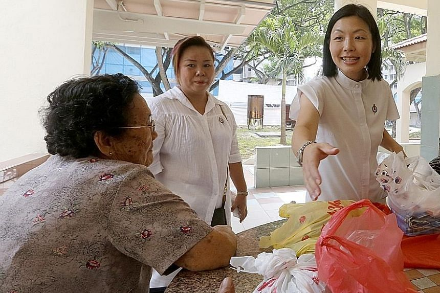 Ms Cheryl Chan reaching out to shake a Fengshan resident's hand during a walkabout in the estate. The PAP rookie politician is facing off against the WP's Dennis Tan in the single-member constituency.