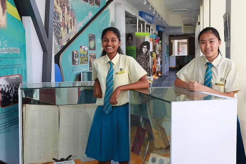 Secondary 3 students S. Darshana (left) and Estella Tan at their school's heritage gallery. Among the items on display are old photos, a handwritten register of students' names and their family details that was used in the 1950s and 1960s, and old sc