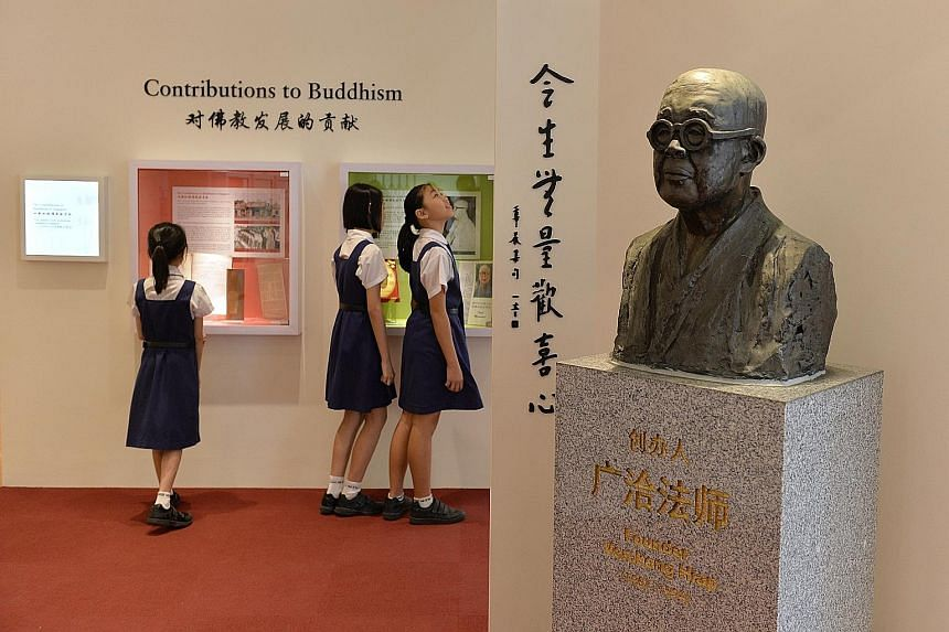 Pupils learning more about the school's contributions to Singapore's Buddhist culture and traditions at the new heritage centre, where a bronze sculpture of Mee Toh's founder, Venerable Kong Hiap, stands guard.