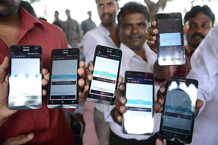 Indian drivers working for Uber, a US-based transport service, with company-issued mobile phones. The drivers alleged they were not making as much money as promised by Uber. Dropped calls could also affect their daily takings.