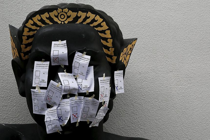 """Mock ballot papers with the option """"No"""" selected pasted on a statue in front of the Bangkok Art and Culture Centre. Students had staged a protest against the military-backed draft Constitution in Bangkok on Saturday."""