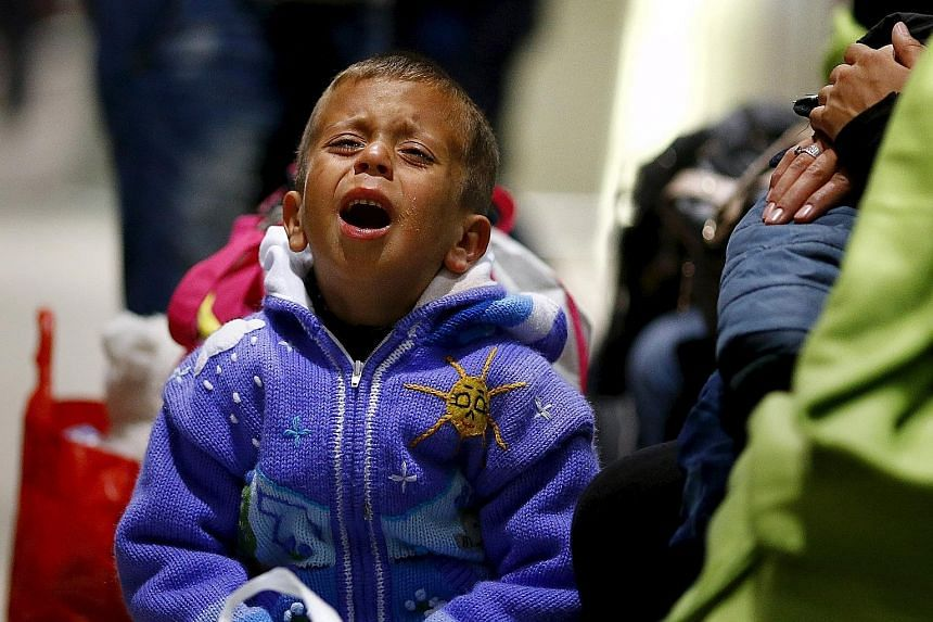 An exhausted Syrian boy crying after he arrived with his family on a train from Budapest's Keleti station at the railway station of the airport in Frankfurt, Germany, early yesterday. The refugee crisis is a responsibility for the rest of the world,