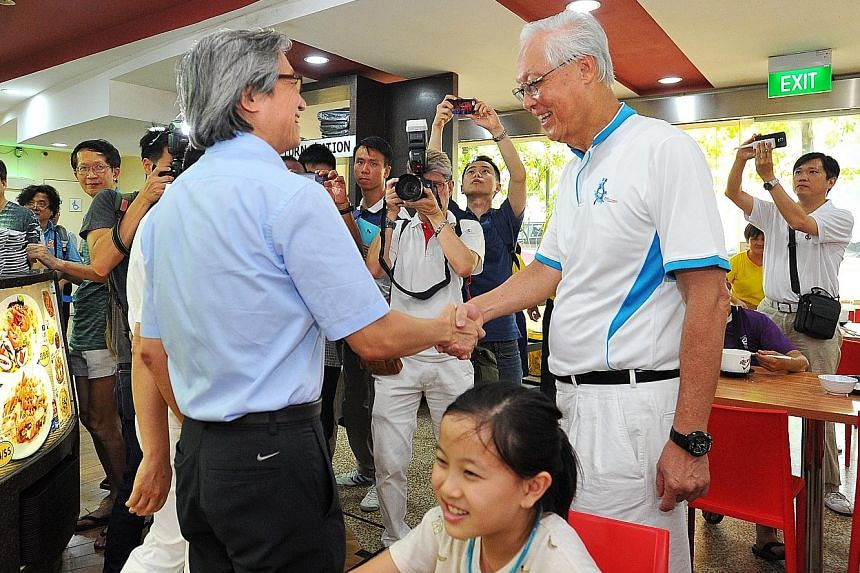 The Workers' Party's Mr Chen Show Mao (left) shaking hands with ESM Goh Chok Tong at a food court in Hougang Central when they met in the opposition-held ward yesterday. GE2015 REPORTS A4-12