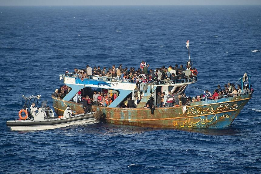 French Navy crew members helping in the rescue of migrants in the Mediterranean Sea, as part of the operation Triton, in coordination with the Frontex agency.