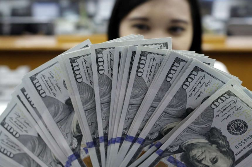 An Indonesian employee preparing US dollar banknotes at a money changer in Jakarta, Indonesia, on Aug 25, 2015.