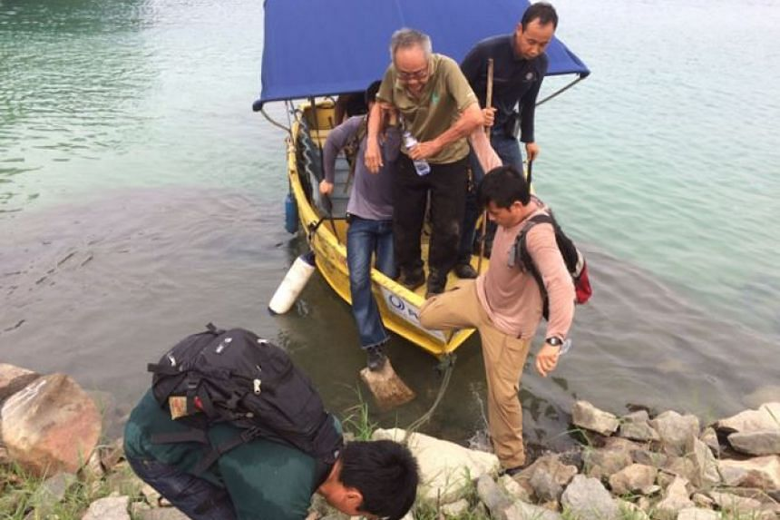 Mr Ng Kang Leng being helped off a boat by rescuers.