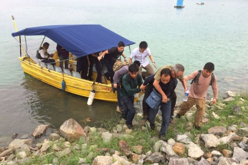 Mr Ng Kang Leng being carried by rescuers after getting off the boat.