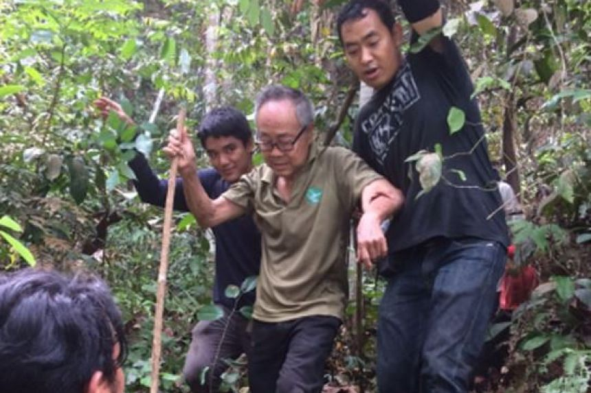 Mr Ng Kang Leng being supported by rescuers.