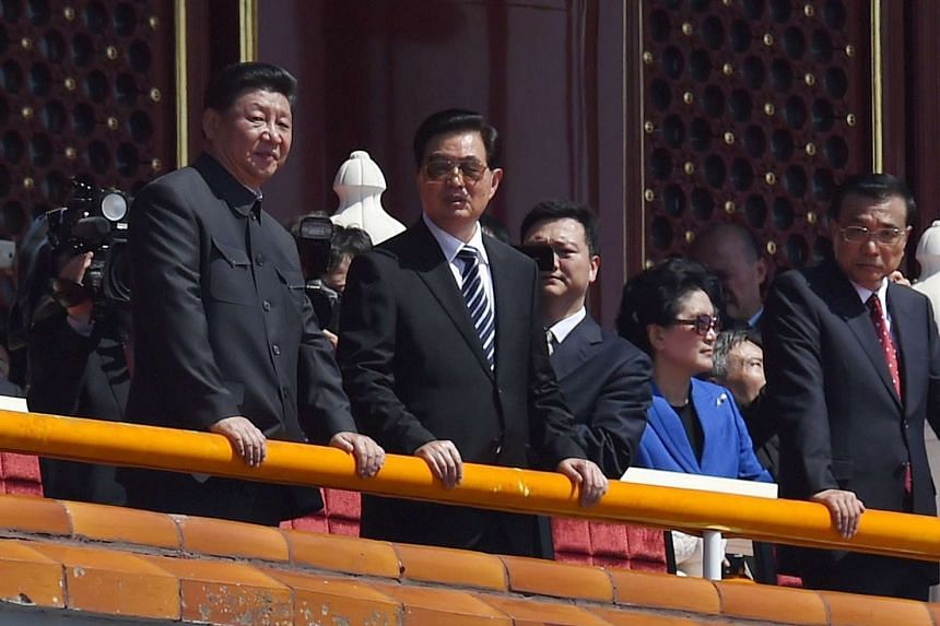 Chinese President Xi Jinping (left) speaking with his predecessor Hu Jintao as Premier Li Keqiang (right) looks on during a military parade to mark the 70th anniversary of the end of World War II, in Tiananmen Square in Beijing on Sept 3, 2015.