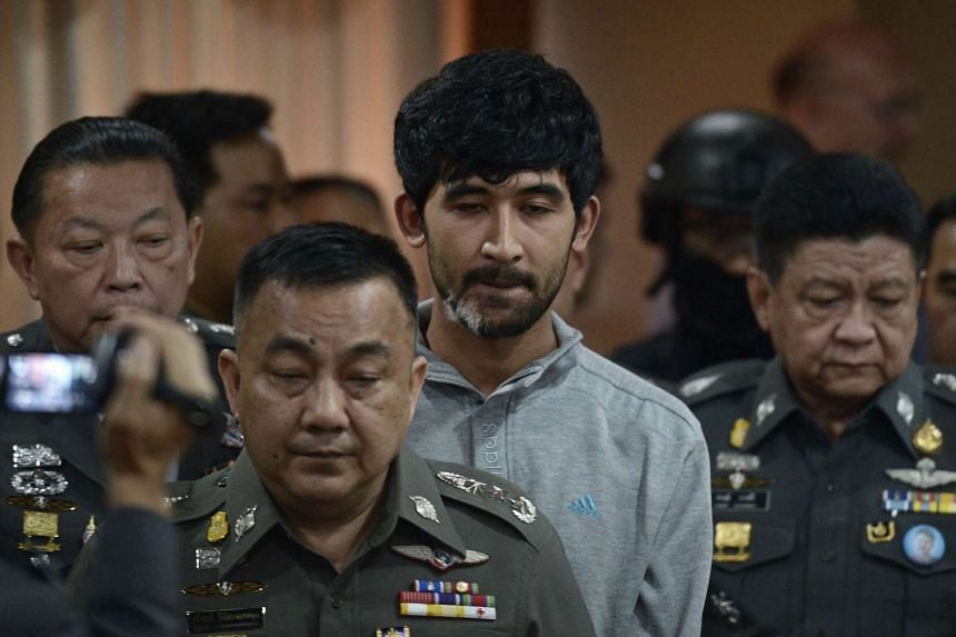 Suspect Yusufu Mieraili (centre), one of those suspected to be involved in the Aug 17 Bangkok bombing, is escorted by policemen at Bangkok's Metropolitan Police Station on Sept 7, 2015.