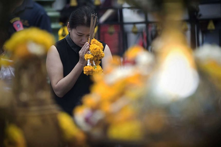 A woman prays in front of the Brahma statue at the Erawan shrine in central Bangkok on Sept 4, 2015