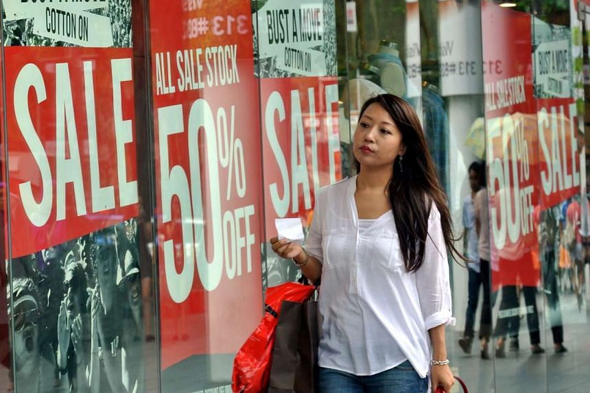 A woman walking past advertisements for the Great Singapore Sale.