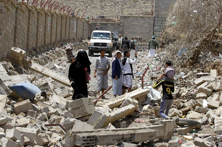 Yemenis walk in the rubble of destroyed buildings in the Al-Nahda neighbourhood of the capital Sana'a, following intensified Saudi-led coalition air strikes, on Sept 6, 2015.