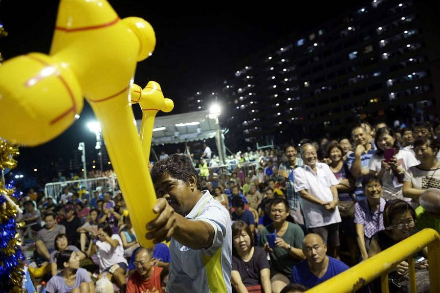A Workers' Party supporter brandishing two toy hammers - the party's symbol - at its rally in Simei on Sunday night. East Coast GRC is expected to be one of the most hotly contested seats in this election.