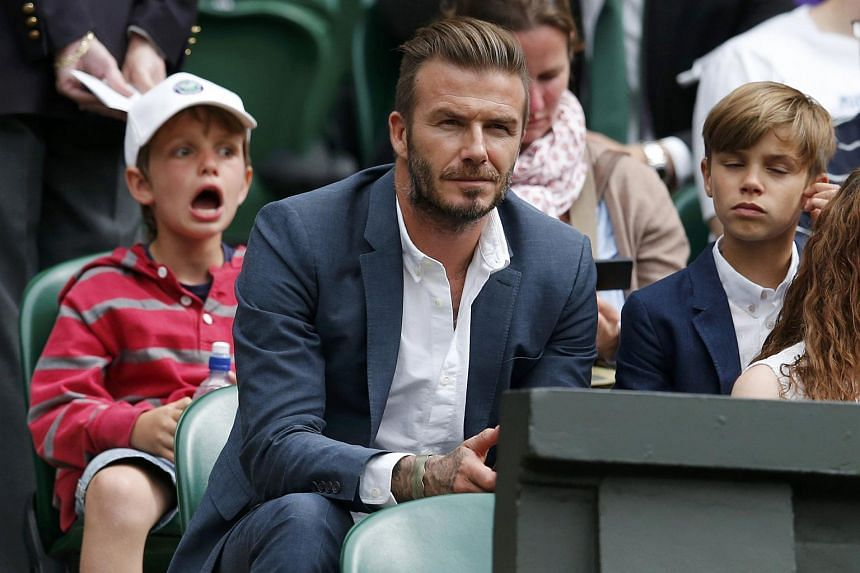 Former footballer David Beckham and his son Romeo on Centre Court at the Wimbledon Tennis Championships in London, July 8, 2015.