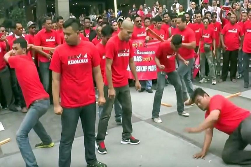 """A red-shirted group put on a """"self-defence"""" display just days before Bersih's rally on Aug 29-30. Members broke wood and roof tiles on one another's backs and heads, in what was seen as a warning to supporters of the Bersih rally."""