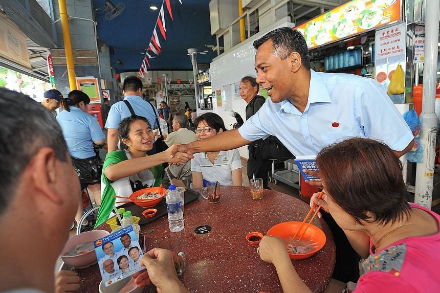 Mr Firuz Khan (standing), a Workers' Party candidate for Marine Parade GRC, at a hawker centre in Marine Terrace on Sunday. Mr Edwin Tong, a People's Action Party candidate for Marine Parade GRC, has been making his rounds in Joo Chiat on a bicycle o