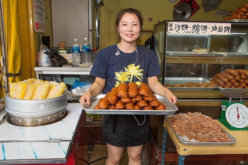 Ms Zhang Ling, who is from Yanbian, does a good trade selling ma hua, a Chinese snack.