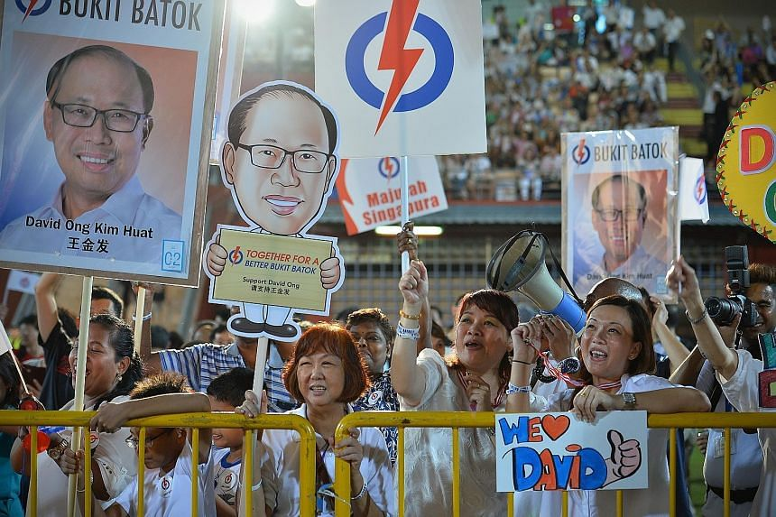 Mr David Ong's supporters holding up placards and signs at the PAP rally at Jurong East Stadium last night.