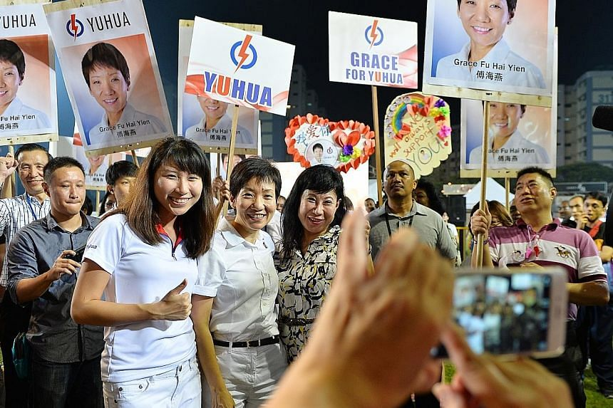 (Above) The PAP candidate for Yuhua SMC, Ms Grace Fu (front row, centre), taking a picture with her supporters at the party's rally in Jurong East Stadium last night.