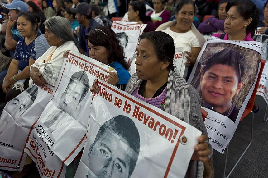 Relatives and friends (above) of the 43 missing students waiting for experts from the Inter-American Commission on Human Rights to present the conclusions of their investigation on Sunday.