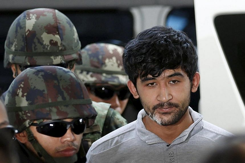 """Bombing suspect Yusufu Mieraili, who the police say was arrested near the Cambodian border, being taken to a police station in Bangkok yesterday. He said he and four others reported to a man known as """"Izaan""""."""