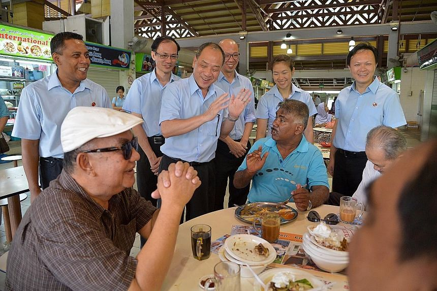 Mr Low Thia Khiang (clapping), secretary-general of the Workers' Party, with Marine Parade GRC candidates (from left) Firuz Khan, Yee Jenn Jong, Terrence Tan, He Ting Ru and Dylan Ng chatting with some diners at the Geylang Serai market yesterday. Th