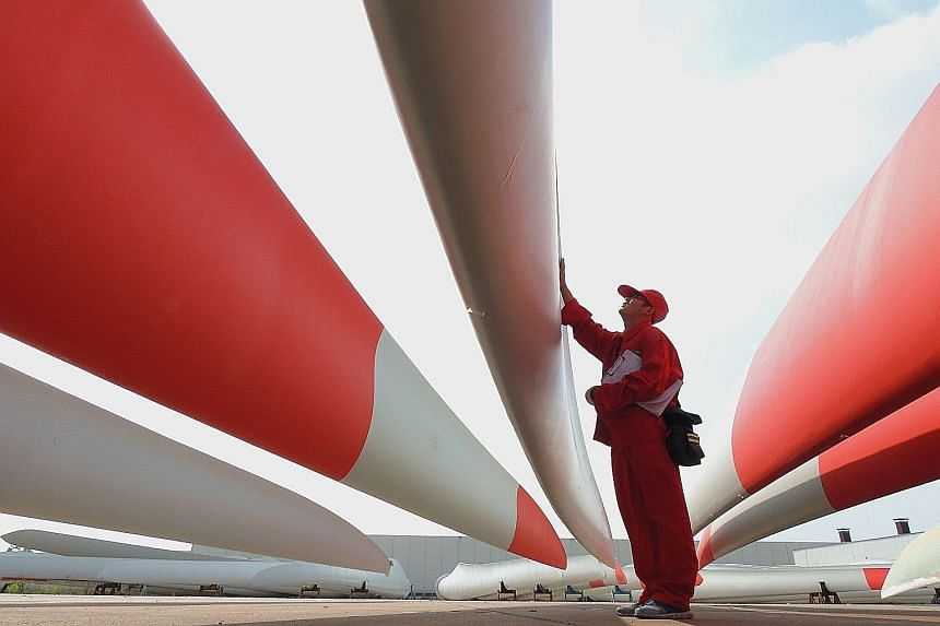 A worker checking wind-turbine blades in a Jiangsu factory. Many Asian markets fell after China cut its 2014 growth figure to 7.3 per cent.