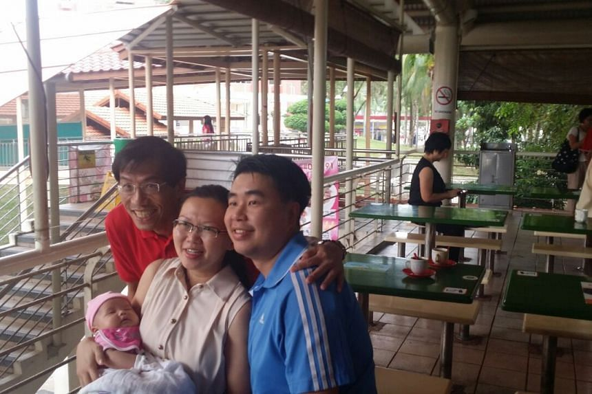 Dr Chee taking a picture with Mr Leow Wee Yee, his wife and baby at Bukit Timah Food Centre on Sept 8, 2015.
