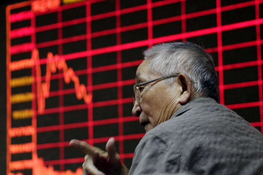 An investor chats in front of an electronic board showing stock information at a brokerage house in Beijing.