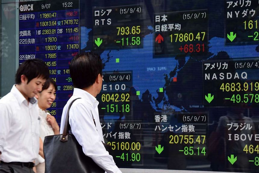 Pedestrians walking past a share prices board in Tokyo on Sept 7, 2015.