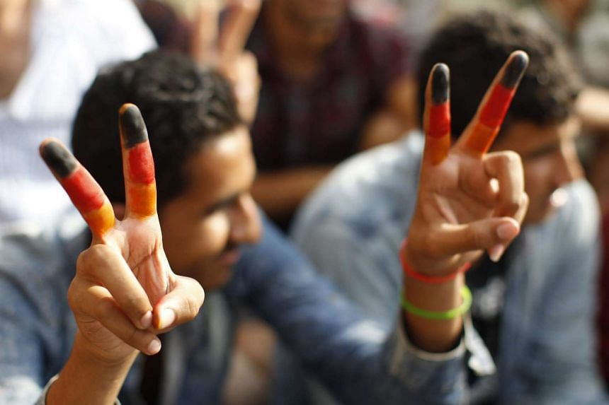 A migrant with fingers painted in the colours of the German national flag at the Keleti Railway Station in Budapest, Hungary, on Sept 3, 2015.