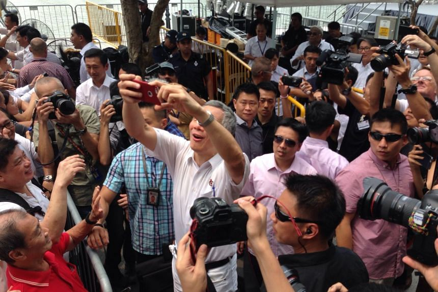 PM Lee taking a photo of the crowd after the PAP lunchtime rally at UOB Plaza promenade on Sept 8, 2015.
