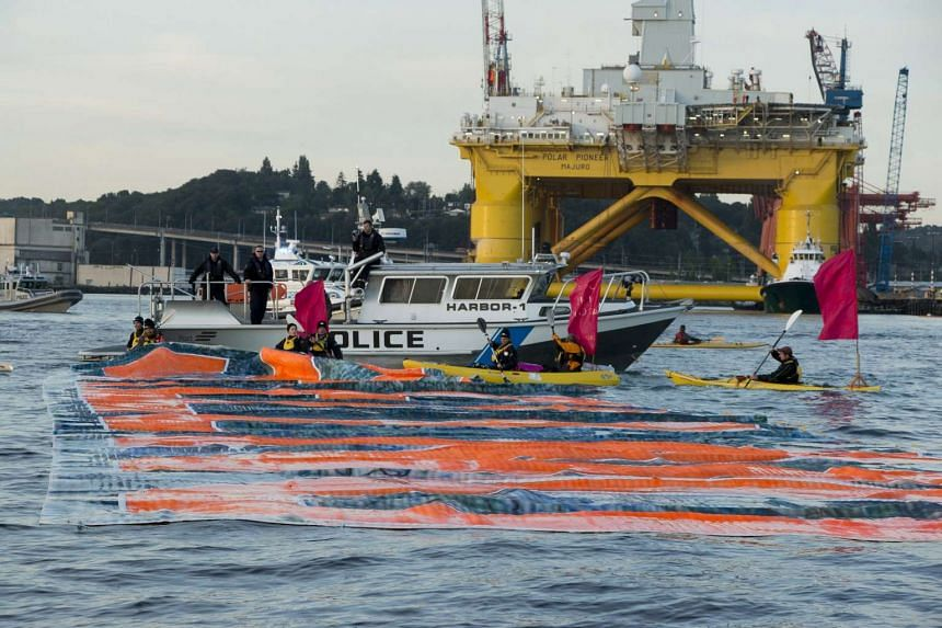 """Environmental activists put a """"Shell No"""" banner on the waters in front of Shell's Drilling Rig Polar Pioneer as it leaves Seattle's Elliott Bay bound for Alaska, in this Greenpeace handout photo taken June 15."""