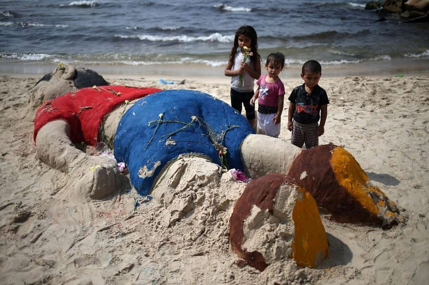 Palestinian children put flowers Monday on a sand sculpture on Gaza city beach depicting Syrian refugee Aylan Kurdi, the three-year-old boy who drowned off Turkey.