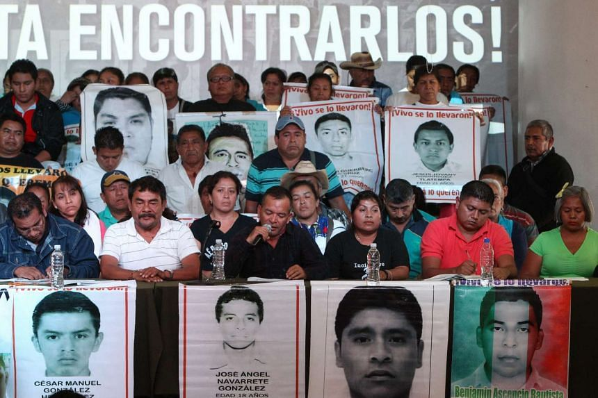 Parents of the 43 young people, who went missing a year ago in Iguala, Mexico, and students of Ayotzinapa school hold pictures of the missing during a press conference in Mexico City, Mexico on Sunday.