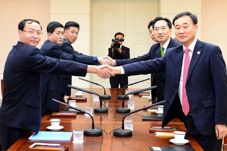South Korean chief delegate Lee Deok-Haeng (2nd right), executive committee member of South Korean Red Cross, shaking hands with his North Korean counterpart Pak Yong-Il (2nd left) during their meeting at the border truce village of Panmunjom on Sept