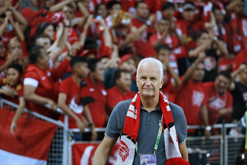 Singapore's coach Bernd Stange standing in front of spectators at the Sports Hub.