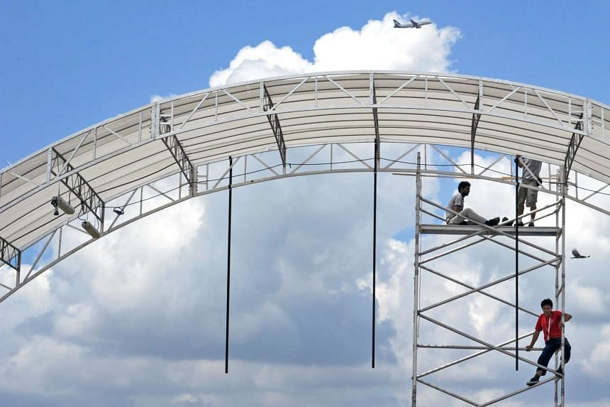 Workers setting up a tentage at the Singapore Airshow in 2012.
