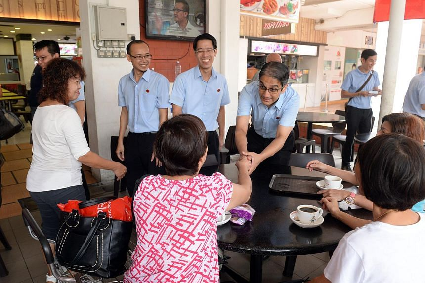 Workers' Party East Coast GRC candidates (from left) Daniel Goh (behind the lady in white), Mohamed Fairoz Shariff, Gerald Giam and Leon Perera chatting with diners at a coffeeshop in Simei on Sept 8, 2015.