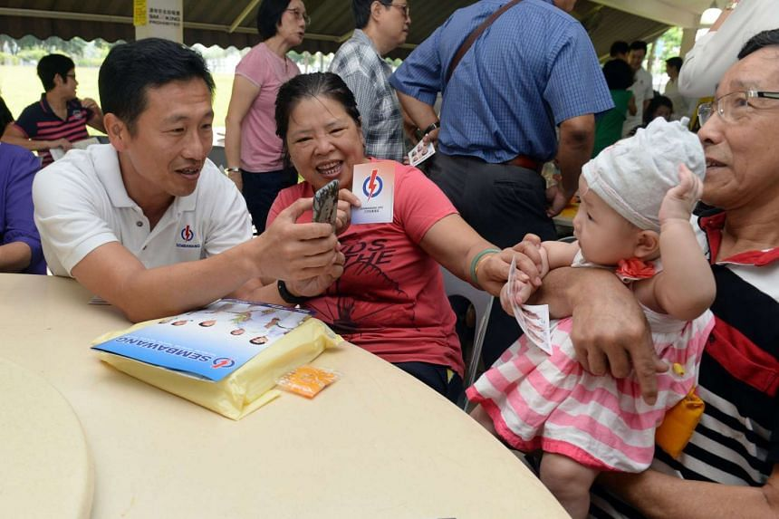 The PAP's Ong Ye Kung, who is contesting Sembawang GRC, taking pictures of residents during a walkabout on Sept 7, 2015.