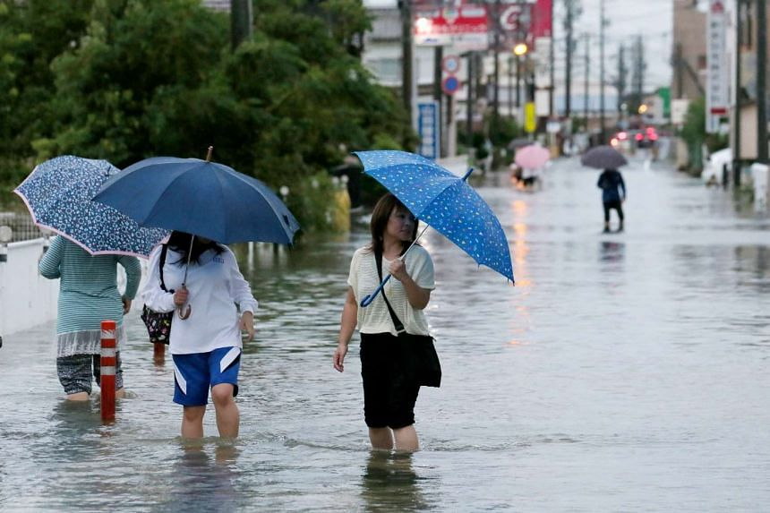 Pedestrians wading through floodwaters following torrential rains brought on by Typhoon Etau in Hamamatsu in Shizuoka prefecture, central Japan, on Sept 8, 2015.