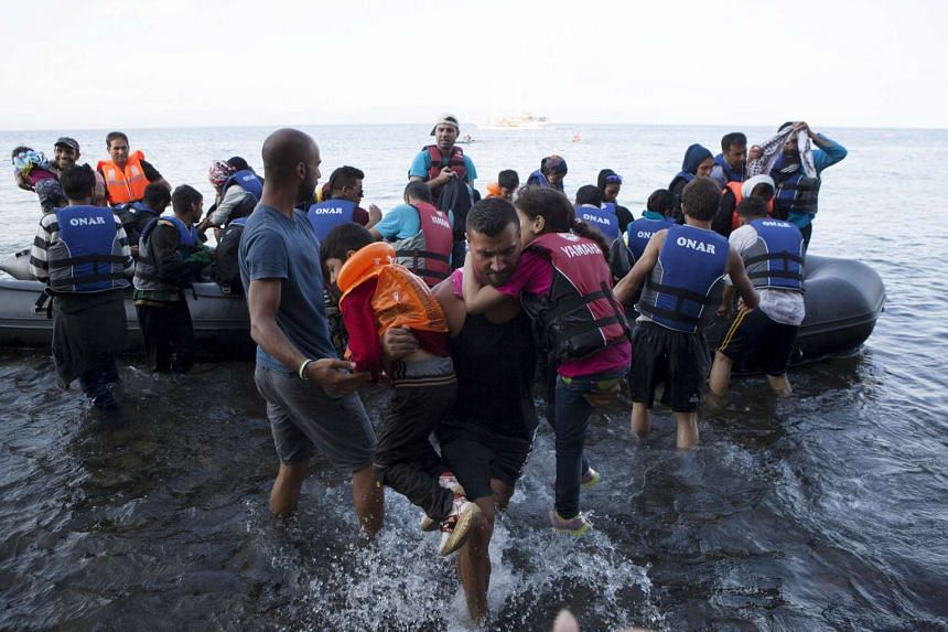 A Syrian refugee carries two children moments after arriving on a dinghy on the Greek island of Lesbos on Sept 8, 2015.