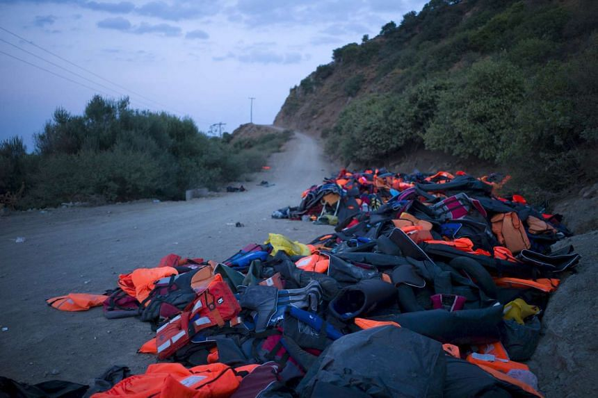 Life jackets, deflated dinghies and life tubes left behind by refugees and migrants are seen on the roadside near a beach on the Greek island of Lesbos on Sept 8, 2015.