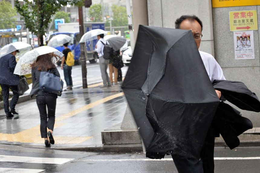 Pedestrians fighting strong winds and rain in Tokyo on Sept 9, 2015.