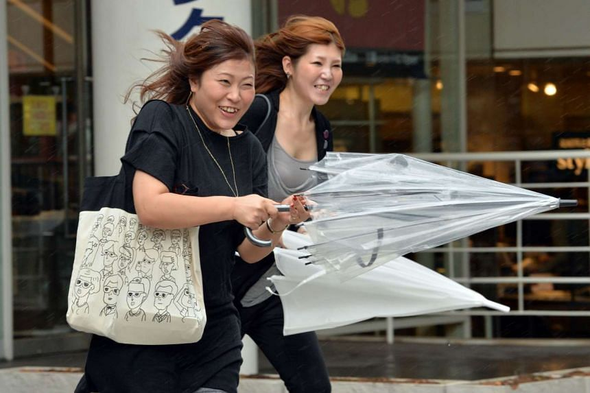 Pedestrians fighting strong winds in Tokyo on Sept 9, 2015.