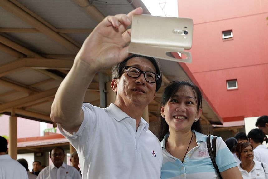 Manpower Minister Lim Swee Say of East Coast GRC taking a picture with a resident at Bishan MRT station on Sept 2, 2015.