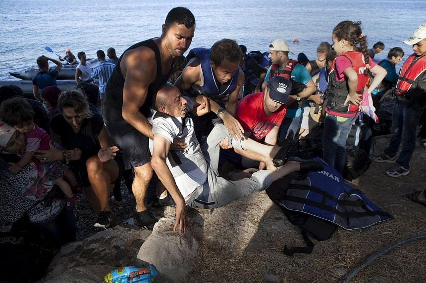 A Syrian refugee is helped by others moments after arriving on a dinghy on the Greek island of Lesbos on Sept 8, 2015.