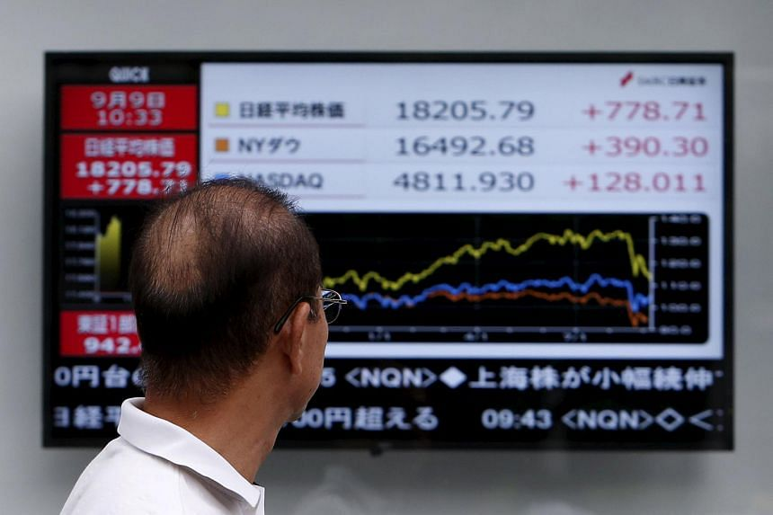 A pedestrian looks at an electronic board showing the graph of the recent fluctuations of market indices of, Japan's Nikkei average, Dow Jones and NASDAQ outside a brokerage in Tokyo, Japan on Sept 9, 2015.