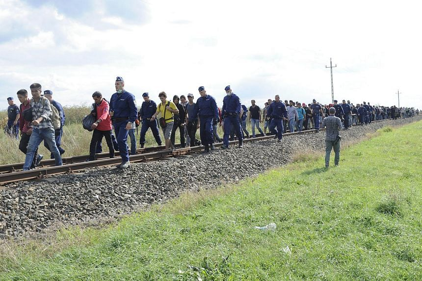 Migrants who left the police reception centre in Roszke in order to avoid being registered walking along the railway tracks connecting Horgos and Szeged, on Sept 8, 2015.